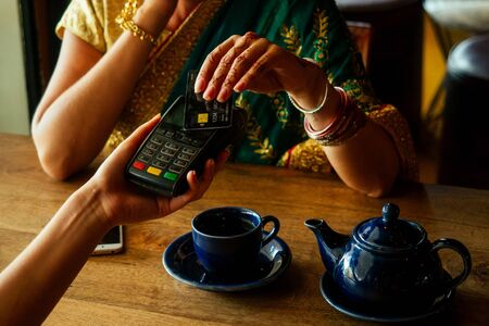 Young indian businesswoman in green traditional sari on a coffee break. Using payment terminal paying by credit card in a cafe restaurant.black friday sale. Фото со стока