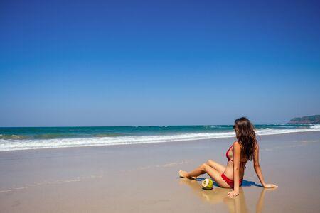 beautiful tanned female fitness model seat near blue sea Stockfoto