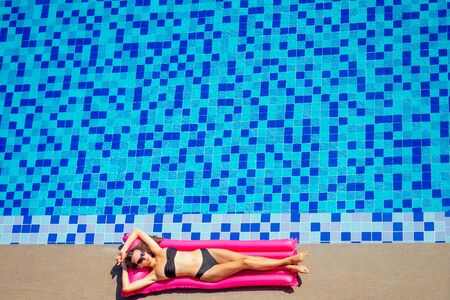 Sexy female model have a rest and sunbath on a float in the pool, top view aerial shot.woman in a black bikini swimsuit floating on an inflatable pink mattress spf and sunscreen.