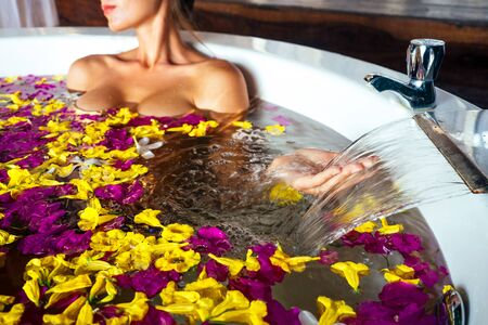 tourist sexy girl taking a bath with tropical flowers on vacation in an exotic summer country.young beautiful woman in round jacuzzi eco hotel spa salon relaxing aromatherapy and massage womens 写真素材