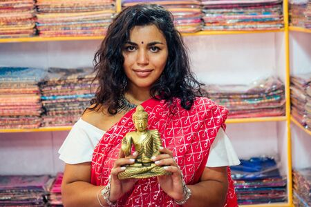 business lady indian seller tradition red sari souvenir shop buddha shiva figurine yoga meditation.girl in india in the religion store.beautiful woman with bijouterie jewelry earrings Delhi Bazaar.