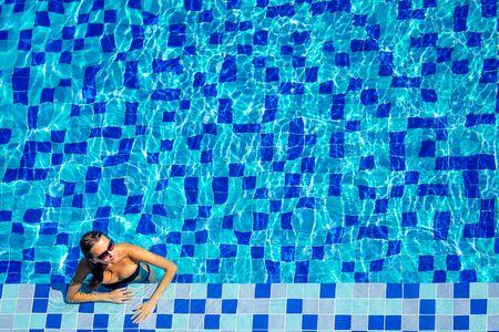 vista dall'alto resort e spa vacanza villa giovane donna che nuota in piscina godendosi una soleggiata giornata estiva in un paradiso tropicale vista dall'alto.
