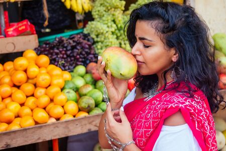 travel girl seller in street market and a buyer in a fruit shop in india. Stock Photo