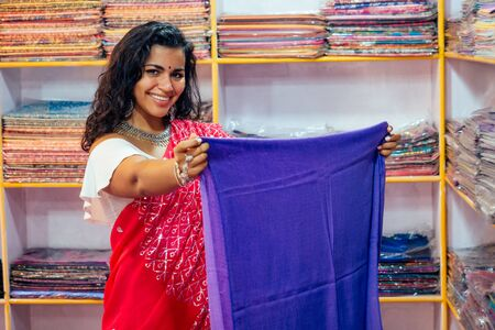 business lady in red traditional sari and jewelery clothes shop owner cashmere yak wool shawls.female seller in goa india arambol sale shop.designer seamstress tailor girl choosing fabric.