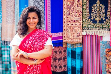 business lady in red traditional sari and jewelery clothes shop owner cashmere yak wool shawls Delhi market.female seller in goa india arambol sale shop.designer seamstress tailor girl in Arambol Goa.