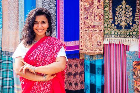 Señora de negocios en sari tradicional rojo y joyería, dueño de la tienda, chales de lana de yak de cachemira, mercado de Delhi, vendedor de mujeres en Goa, India, venta de arambol, tienda.