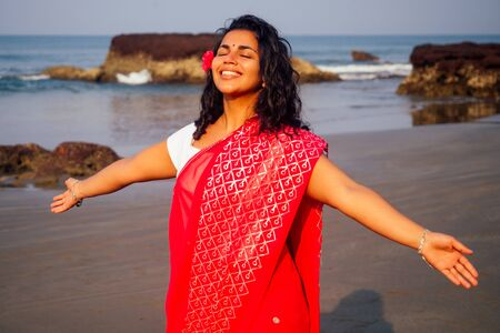 portrait of attractive indian female model in vacation on paradise tropical beach by ocean sea. hindu woman with kundan jewelry set traditional India costume red wedding sari.asian girl sensual look.