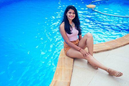 Belle femme indienne sourire blanc à pleines dents selfie portrait sur smartphone appareil photo café d'été au bord de la mer au bord de la piscine goa Banque d'images