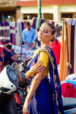 indian beautiful Caucasian woman traditional blue dress.hindu model with golden kundan jewelry set bindi and nose ring piercing nath fashion photoshoot on street among motorcycles and Mapusa market Stock Photo