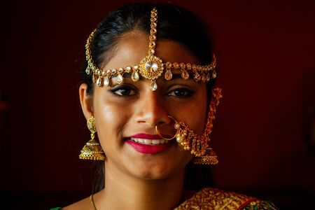 portrait indian beautiful female in golden rich jewelery and tradition saree face closeup professional make-up wearing bindi on head .Muslim Woman face portrait with bindis maang tikka ,nath,nose Pin Stock Photo