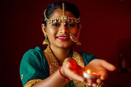 Woman lighting diyas with nuth nath nose piercing and the golden teak with traditionak fashion sari