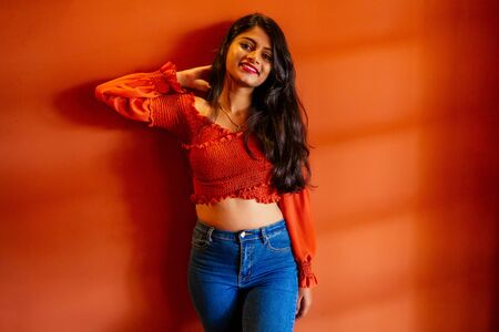 Portrait of a young indian woman in casual style jeans and blouse orange walls city