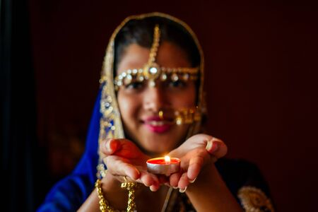 Woman lighting diyas with nuth nath nose piercing and the golden teak with traditional fashion sari Stockfoto