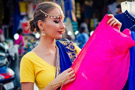business lady indian beautiful Caucasian woman traditional dress.hindu model golden kundan jewelry set bindi earrings and nose ring piercing nath sale shop.designer seamstress tailor choosing fabric