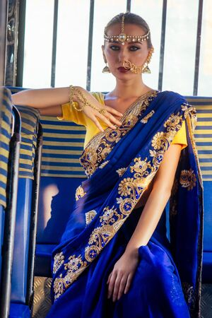 portrait indian beautiful Caucasian woman in traditional blue dress.hindu model with golden kundan jewelry set bindi earrings and nose ring piercing nath fashion photoshoot in bus Stock Photo