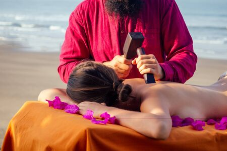 male master makes Thai massage Tok-sen spa therapy physiology by the sea ocean beach.Beautiful woman having a relaxing thai back massage with set for massage toksen,Body care relaxation resort