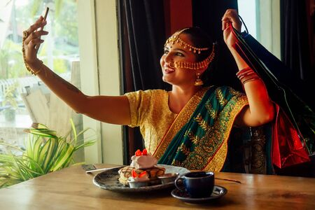 indian woman taking selfie with shopping bags ,pancakes strawberry waffles Tea Coffee cap sitting at cafe next to window .golden bindi and mehendi .sale day shopping black Friday shopping center