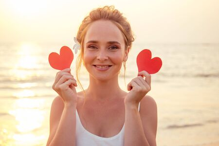 Portrait of happy young woman standing at the Beach. Woman holding a paper red heart Valentine card