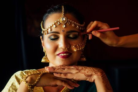 portrait indian beautiful female in golden rich jewelery tradition saree face closeup professional make-up wearing bindi on head ,with bindis maang tikka ,nath,nose Pin.morning of the bride visagiste