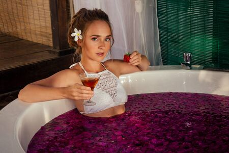 spa ,St. Valentines Day. female model romantic date in jacuzzi with flowers bali eco hotel with candles.woman relaxed in a bath with tropical petals beverage drink.International Womens Day March 8 Stock Photo