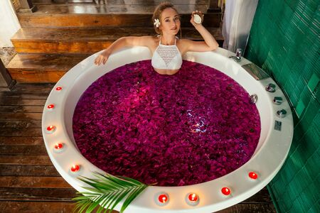 spa care,St. Valentines Day. female model romantic date in jacuzzi with flowers bali eco hotel with candles.woman relaxed in a bath with tropical petals.International Womens Day March 8 Stock Photo