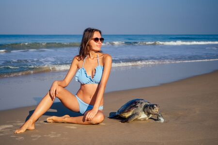 copyspase travel girl posing in a blue bikini swimsuit next to a big male turtle lifestyle vacation paradise untouched deserted beach good morning.tourism guide concept.