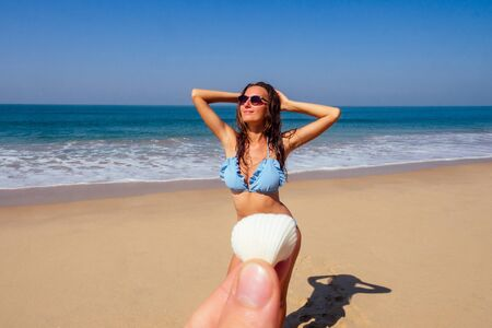 sexy brunette hair woman hands up blue swimsuit large conch shell chest, pov prospective - man holding seashells covering her bikini area epilation removal of unwanted hair pubic pussy