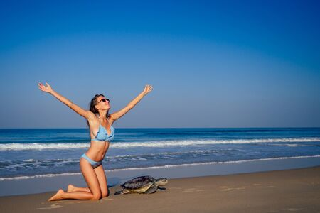 travel girl posing in blue bikini swimsuit looking into the distance and pointing a finger next to a big male turtle lifestyle vacation paradise untouched deserted beach morning.tourism guide concept Stock Photo