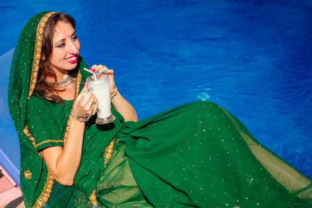 beautiful indian woman in green stylish sari ,toothy white smile while lying on a sun lounger summer cafe by sea by the swimming pool.traditional lassi drink goa.Fruit smoothie healthy eating concept