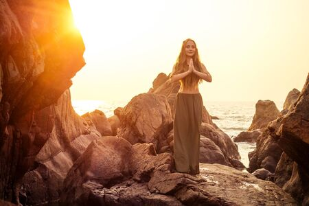 stylish redheaded chestnut blonde young girl in indie bohemian bo-ho style clothes black stylish top.boho woman long hair,makeup and green feathers in head practicing yoga asanas on the rocks by sea Stok Fotoğraf