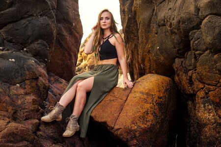 portrait of stylish elegant redheaded chestnut blonde young girl in indie bohemian bo-ho style clothes black stylish top.boho woman long hair,makeup and green feathers in head on the rocks by the sea