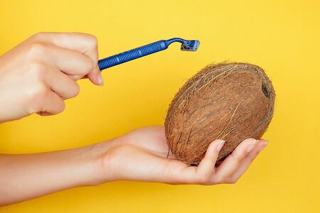 close-up in the palm of hand holding a juicy fruit kiwi and razor on a yellow background . depilation and epilation idea caring for the body