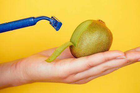 Nahaufnahme in der Handfläche, die eine saftige Fruchtkiwi und ein Rasiermesser auf gelbem Hintergrund hält. Depilation und Epilationsidee zur Pflege des Körpers