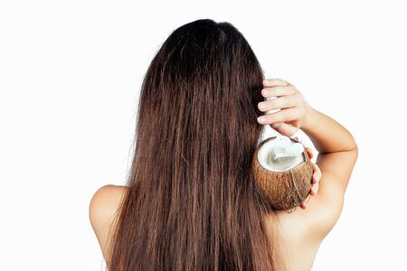 sexy nude indian woman applying coconut oil from the bottle and cap to dark brunette long hair in a hand on white isolate back view