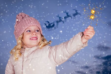 little girl in a knitted hat holding fireworks on darkblue background. Santa flying in sleigh the eve of Christmas snowy sky