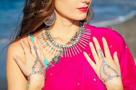 female model earrings and necklace in vacation on paradise tropical beach by ocean sea. hindu woman with kundan jewelry traditional India costume sari.girl near the rocks shores of Indian Ocean bay