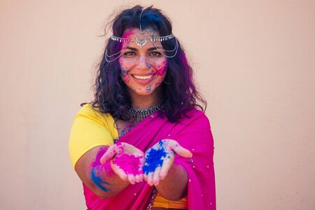 female indian model snow-white smile on holi color festival.Indian Woman in traditional sari dress with black curly hair in a pink and blue paint and bindi jewelry celebrating Holi color festival
