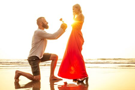 romantic February 14 Valentines Day summer holidays, relationship dating.love couple with bouquet flowers man in a white shirt and a blond woman in a long dress with a rose in his hand on the beach