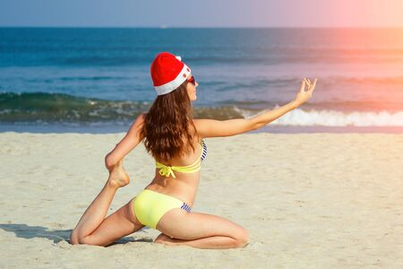 young girl practicing yoga on the beach wearing Santas hat Stock Photo