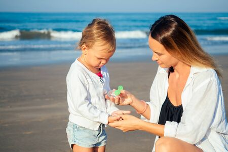 mother and daughter use an antiseptic on the beach