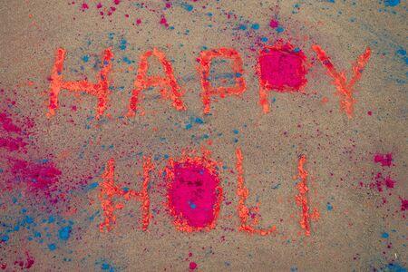 Happy Holi inscription on the sand blue and orange dust holy