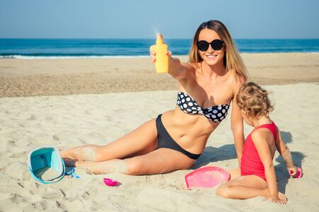 mother sprinkles a sunscreen next to her daughter on the beach