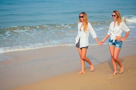 dos amantes y hermosas mujeres están caminando en la playa tomados de la mano