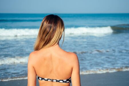 shoulders and back of a woman in a swimsuit on the beach Imagens