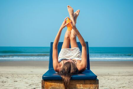 beautiful and sexy young woman is applying sunscreen on the body on the sea. Protection from ultraviolet rays and prevention against skin cancer on vacation