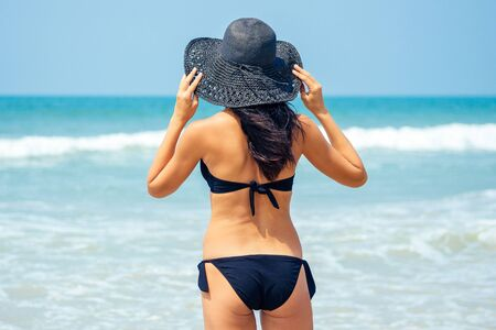 beautiful and young woman standing in a black bathing suit and a black hat on the beach. Holiday in a tropical country