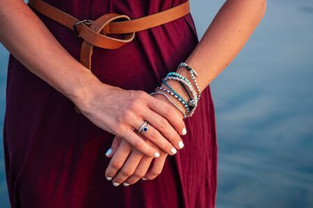 beautiful and well-groomed hands with a natural manicure with chic and elegant bracelets