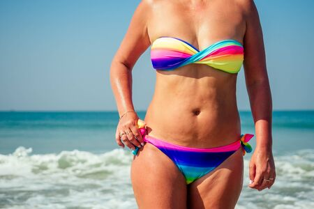 An elderly lady is resting on the beach. Beautiful and colorful bright swimsuit on the flabby and old woman body on the beach