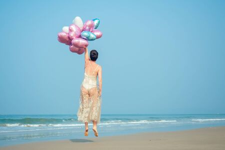 happy and young women exists with short hair holding a brighter and brilliant air balloons. bright balls in the hands of a girl resting on the beach