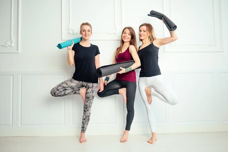 happy group of people three women practicing yoga in fun in the studio. groups of meditation and support in the yoga class. yoga, mate, woman. three women are posing in the gym with a yoga mat